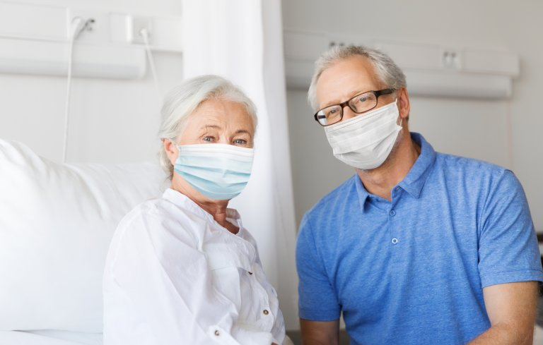 37227886-senior-couple-in-face-masks-meeting-at-hospital-Mostphotos.jpg