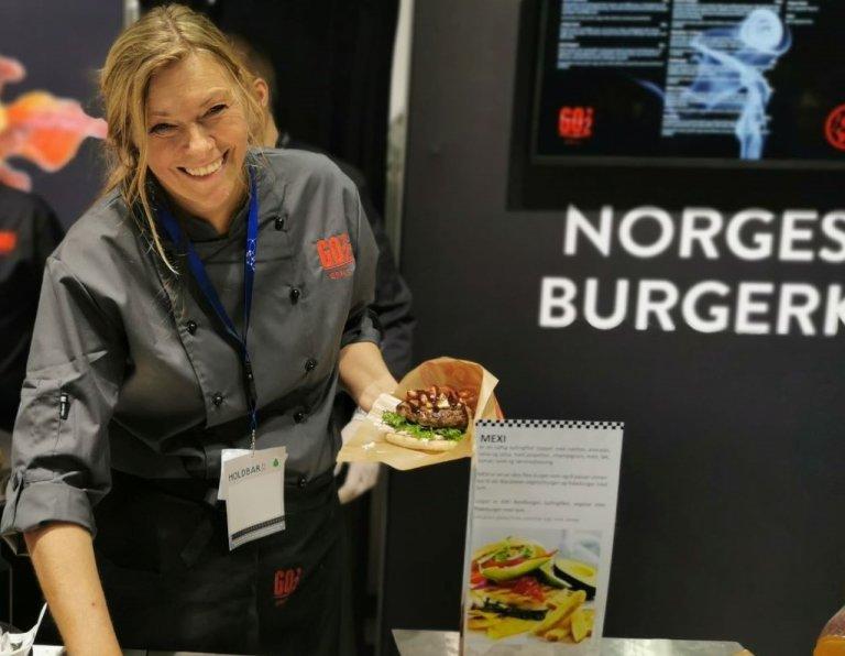 Bilde av Anne-Lise Sørensen fra Patricias gatekjøkken som holder en hamburger. Foto: Karine H. Henriksen, Convenience.