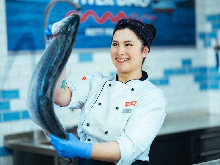 Bilde av dame som holder fisk. Foto MENY.